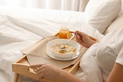Sjuk kvinna som äter ny hemlagad soppa för att kurera influensa i säng hemma royaltyfri fotografi