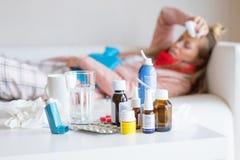 Sjuk kvinna som framme ligger i säng med många mediciner på tabellen royaltyfria foton