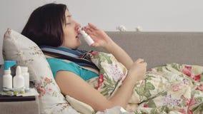 Sjuk kvinna som hemma ligger i säng, sprej i näsa Fotografering för Bildbyråer