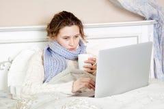 Sjuk kvinna som känner sig dålig, hemma vilar och arbetar med hennes bärbar dator och internet i hennes säng Royaltyfria Bilder