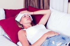 Sjuk kvinna som ligger i säng med hög feber Kall influensa och migrän royaltyfri foto