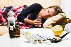 Sjuk kvinna som ligger på soffan under ullfilten Fotografering för Bildbyråer