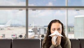 Sjuk kvinna som nyser på flygplatsen arkivfoto