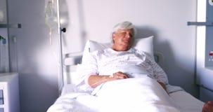 Sjuk kvinna som sover på säng medan bekymrat mansammanträde bredvid hennes säng lager videofilmer
