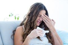Sjuk kvinnagråt på soffan arkivfoton