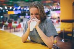 Sjuk kvinnlig student som blåser hans näsa in i ett silkespapper Royaltyfria Foton
