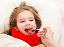 Sjuk liten flicka i säng som tar medicin arkivfoton