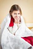 Sjuk liten flicka som hostar på säng under filten Arkivbilder