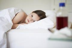 Sjuk liten flicka som ligger i säng arkivfoton
