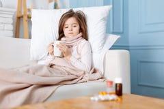 Sjuk liten flicka som ser mediciner royaltyfri fotografi