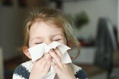 Sjuk liten flicka som täcker hennes näsa med näsduken Arkivbild