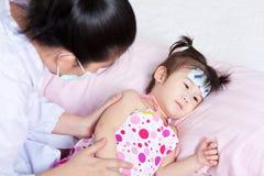 Sjuk liten flicka som vårdas av ett pediatriskt Arkivbilder
