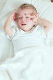 Sjuk litet barnpojkegråt i säng Arkivfoton