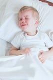 Sjuk litet barnpojkegråt i säng Royaltyfria Bilder