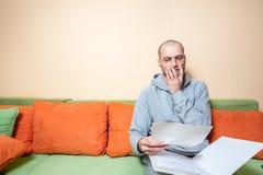 Sjuk man för ung eller mellersta ålder i den tillfälliga kläderna som läser medicinska resultat på legitimationshandlingar från h arkivfoton