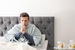 Sjuk man med hostalidande från förkylning i säng Arkivfoto