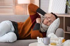 Sjuk man med huvudvärklidande från förkylning på soffan hemma Fotografering för Bildbyråer