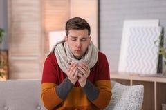 Sjuk man med koppen av varmt drinklidande från förkylning på soffan hemma Arkivbilder