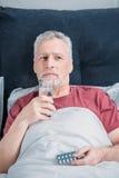 Sjuk man med mediciner och exponeringsglas av vatten i säng Royaltyfri Fotografi