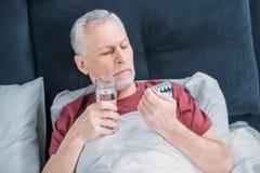 Sjuk man med mediciner och exponeringsglas av vatten i säng Arkivfoto
