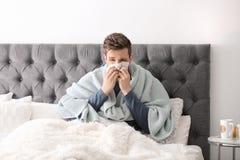 Sjuk man med silkespapperlidande från förkylning i säng Arkivbilder