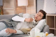 Sjuk man med silkespapperlidande från förkylning på soffan hemma Royaltyfria Bilder