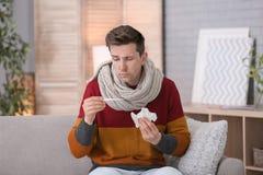 Sjuk man med termometerlidande från förkylning på soffan hemma Arkivfoto