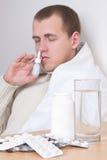 Sjuk man som använder nasal sprej i vardagsrum Arkivfoto