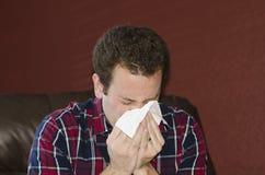 Sjuk man som blåser hans näsa in i ett silkespapper Fotografering för Bildbyråer