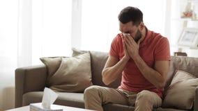 Sjuk man som blåser näsan för att skyla över brister wipen hemma arkivfilmer