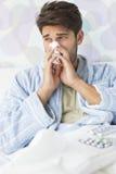 Sjuk man som hemma blåser hans näsa i silkespapperpapper på säng Royaltyfri Bild