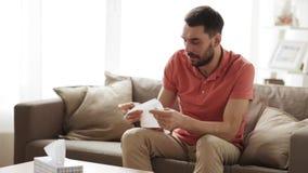 Sjuk man som hemma blåser näsan till den pappers- servetten arkivfilmer