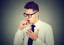 Sjuk man som hostar med näven för nasal droppande för stolpe den hållande för att skvallra arkivbilder
