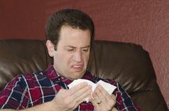 Sjuk man som ser ett silkespapper, når att ha blåst hans näsa Royaltyfria Foton