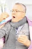 Sjuk man som täckas med filten som tar en preventivpiller Arkivbild