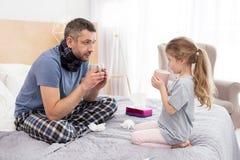 Sjuk pappa och hans dotter som dricker varmt te Arkivfoton