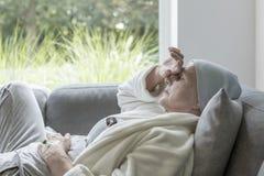 Sjuk pensionär med en hand på en panna som ligger på en soffa fotografering för bildbyråer