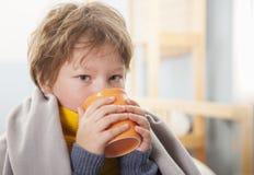 Sjuk pojke med en kopp te hemma royaltyfri bild