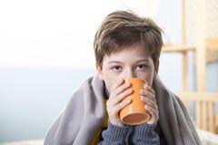 Sjuk pojke med en kopp te hemma royaltyfri fotografi