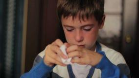 Sjuk pojke som blåser hans näsa in i en servett medan