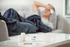 sjuk sl?sad man som ligger i soffan som har medicinminnestavlor royaltyfria bilder
