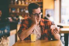 Sjuk student som blåser hans näsa in i ett silkespapper Arkivbild
