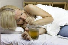 Sjuk ung blond kvinna som rymmer en kopp av grönt te och hostar på soffan arkivbild