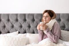 Sjuk ung kvinna med koppen av varmt drinklidande från förkylning i säng Arkivfoto