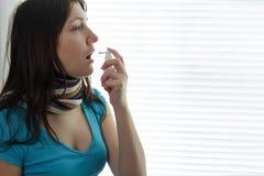 Sjuk ung kvinna- och halssprej Fotografering för Bildbyråer