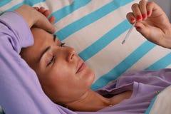 Sjuk ung kvinna som ner ligger på säng Royaltyfri Foto
