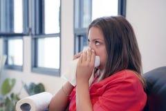 Sjuk ung kvinna som sitter på en svart soffa och blåser hans näsa royaltyfria foton