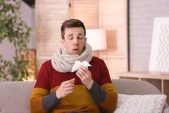Sjuk ung man med silkespapperlidande från förkylning Arkivfoto