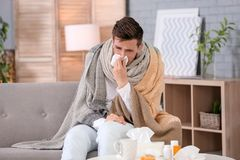 Sjuk ung man med silkespapperlidande från förkylning Arkivbilder