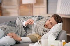 Sjuk ung man med termometerlidande från förkylning Royaltyfria Bilder